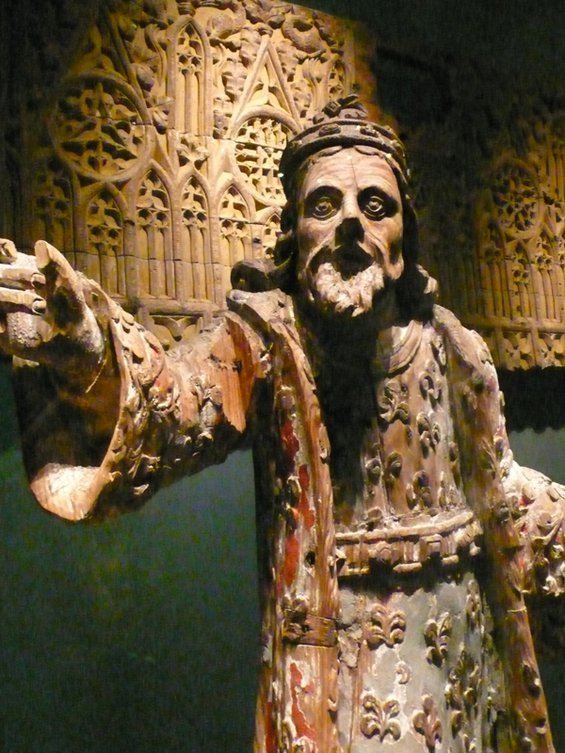 Medieval wooden sculpture of a bearded man with his hand outstretched toward the viewer in the National Museum of Iceland