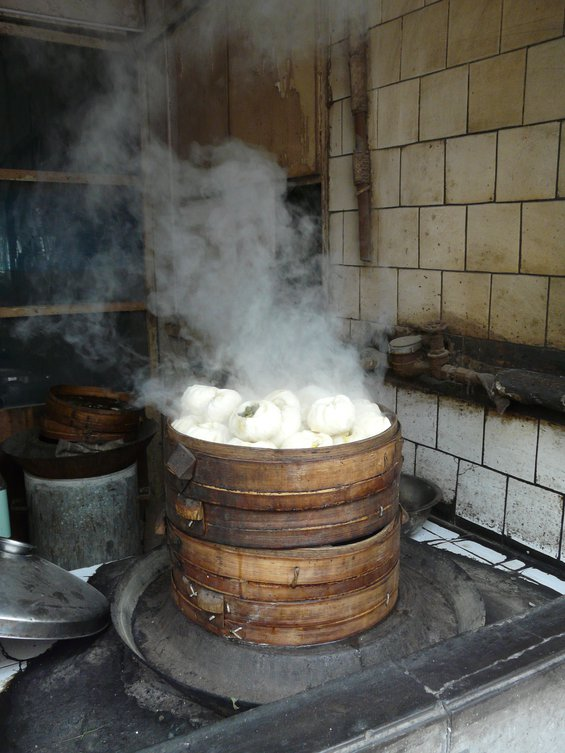 An example of street food in China: a tall, wooden pot full of hot, steaming white buns
