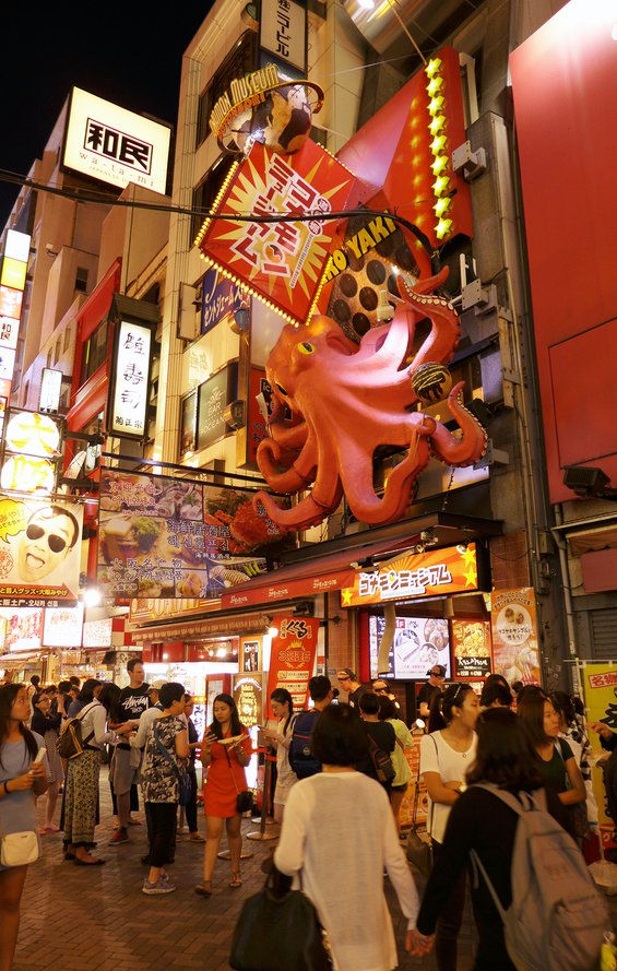 shoppers walking the night market on Dotonbori street in Osaka below a large 3D pink octopus sign