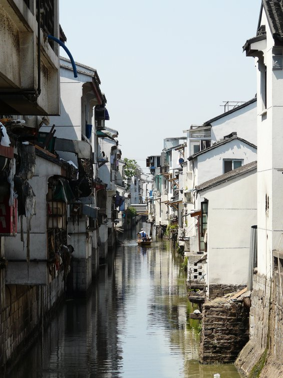 View of houses in Suzhou, China, on either side of a canal with an inhabitant poling his way down the canal in a boat