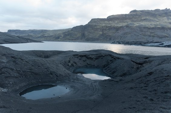 Dark grey Icelandic glaciers with two almost circular pools of water in the foreground and a long stretch of water in the middleground.