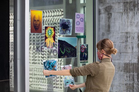 Director of Exhibitions Jaime Austin installs the CCA@CCA Artwork Campaign in the windows of the CCA Hubbell Street Galleries. Photo by Nicholas Lea Bruno.