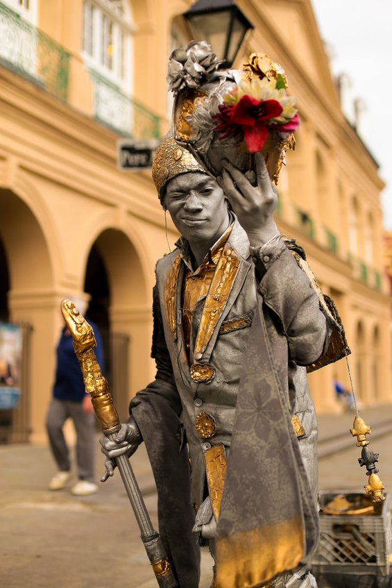 A New Orleans street performer in silver paint, winking at the viewer