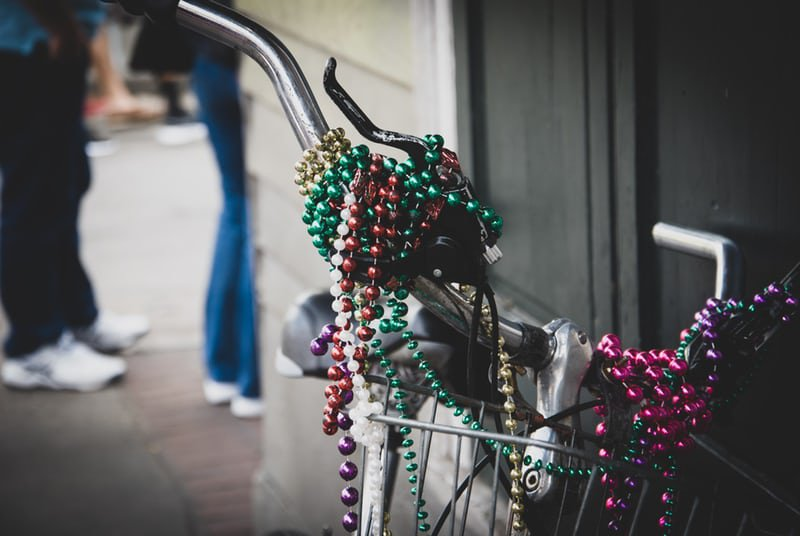 Colorful strands of Mardi Gras beads strung on bike handles