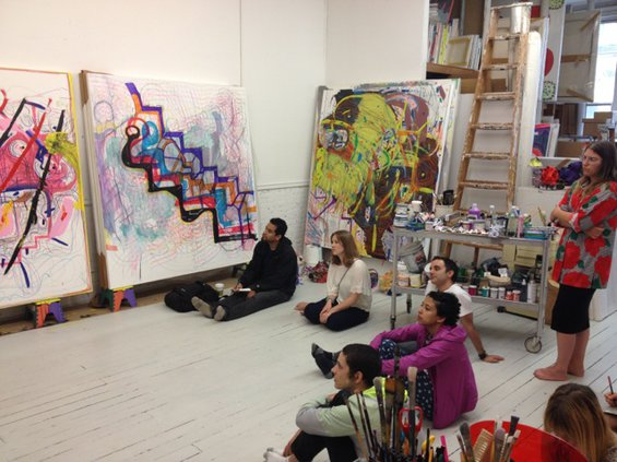 group of students, sitting on the floor in a semi-circle, with artist Joanne Greenbaum standing behind them, discussing paintings leaning against a wall