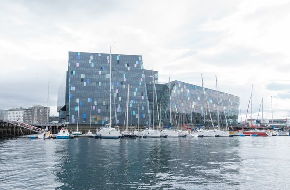 Sailboats lined up in front of the modern Harpa Concert Hall, covered in blocks of iridescent color, shimmering like the sea