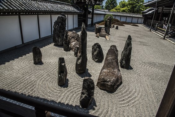 garden at Tofuku-ji Temple in Kyoto with white pebbles raked into a swirling pattern around the base of large, dark, irregularly shaped standing rocks