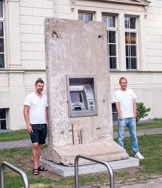 """Elmgreen and Dragset posing on either side of their """"Statue of Liberty,"""" a 24-hour ATM set in a rectangular concrete slab."""